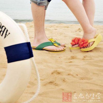 两个人并肩牵着手走在海边的沙滩上