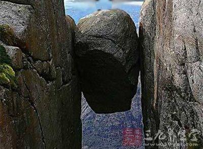 这块5立方米距谷底约1000米的石头卡在山间的绝壁间