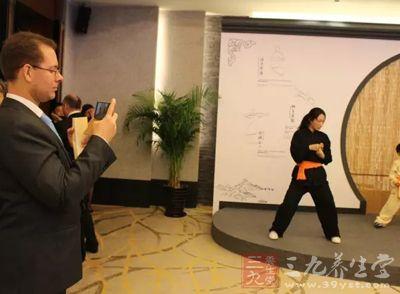 外宾拿起手机对易筋经等健身功法表演进行录像
